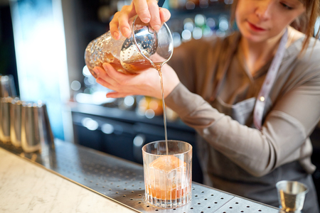 alcohol drinks, people and luxury concept - woman bartender with glass and jug preparing cocktail at bar