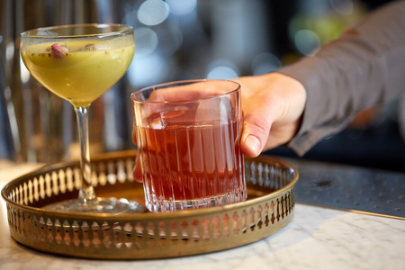 alcohol drinks, people and luxury concept - bartender putting glasses of cocktails to tray at bar 版權商用圖片