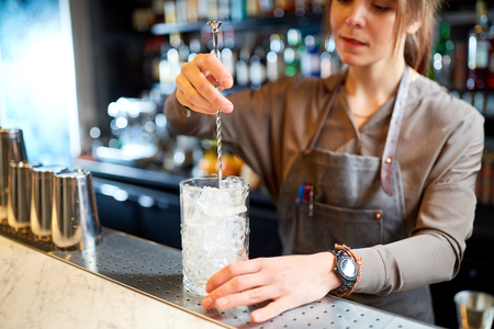alcohol drinks, people and luxury concept - woman bartender with stirrer and glass of ice preparing cocktail at bar counter