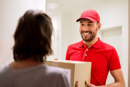 addressee: delivery, mail, people and shipping concept - happy man delivering parcel box to customer home Stock Photo
