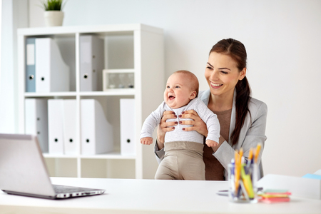 multi tasking: business, motherhood, multi-tasking, family and people concept - happy smiling businesswoman with baby working at office