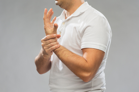 people, healthcare and problem concept - close up of man suffering from pain in hand over gray background Stock Photo