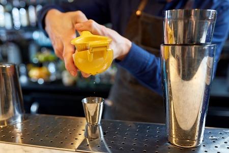 alcohol drankjes, mensen en luxe concept - barman met shaker en citruspers knijpen sap in jigger en voorbereiding cocktail in bar