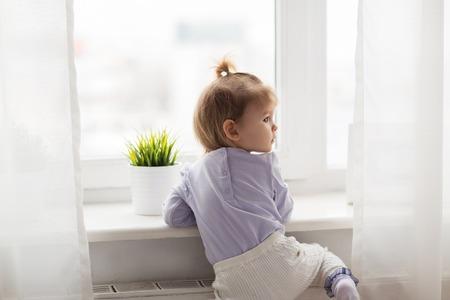 乳幼児: 幼年期、子供および人々 のコンセプト - ホーム ウィンドウで素敵な女の子 写真素材