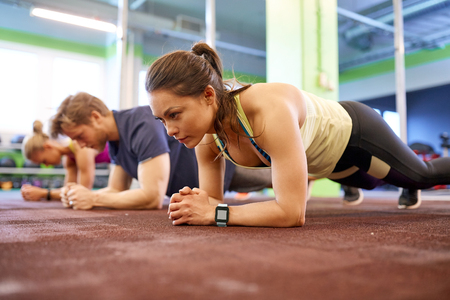 fitness, sport, exercising and people concept - woman with heart-rate tracker at group training doing plank exercise in gym Stock Photo