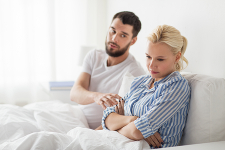 people, relationship difficulties and family concept - unhappy couple having conflict in bed at home Stock Photo