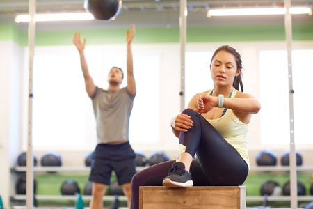 sport, training and people concept - man exercising with medicine ball and woman tracking time on fitness tracker in gym Stock Photo - 77346121