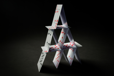 casino, gambling, games of chance, hazard and insecurity concept - house of playing cards over black background Stock Photo