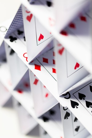 ephemeral: casino, gambling, games of chance, hazard and insecurity concept - close up of house of playing cards over white background