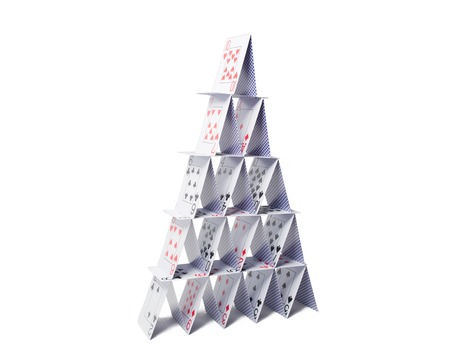 casino, gambling, games of chance, hazard and insecurity concept - house of playing cards over white background Imagens