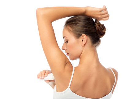 underarm: beauty, hygiene, bodycare and people concept - beautiful young woman applying antiperspirant or stick deodorant over white background