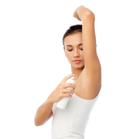 schoonheid, hygiëne, lichaamsverzorging en mensen concept - mooie jonge vrouw aanbrengen van antiperspirant of spray deodorant op witte achtergrond Stockfoto
