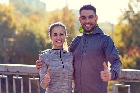approvement: smiling couple showing thumbs up outdoors Stock Photo