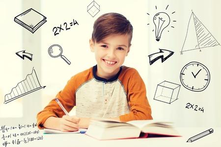 lachende student jongen schriftelijk aan notebook thuis Stockfoto
