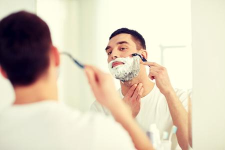 bathroom mirror: man shaving beard with razor blade at bathroom