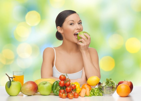 woman with fruits and vegetables eating apple