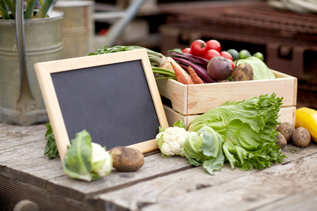 close up of vegetables with chalkboard on farm Stock Photo