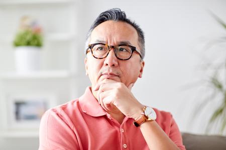 asian man thinking at home