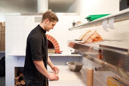 chef preparando pizza masa en la cocina en la pizzería