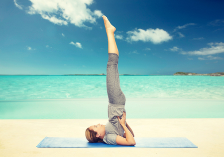 woman making yoga in shoulderstand pose on mat Stock Photo - 77851466