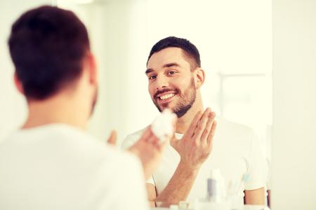 bathroom mirror: happy man applying shaving foam at bathroom mirror