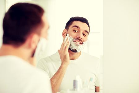 groomed: happy man applying shaving foam at bathroom mirror