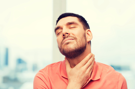 unhappy man suffering from throat pain at home Stock Photo