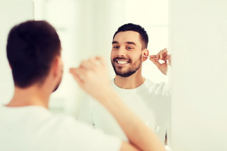man cleaning ear with cotton swab at bathroom