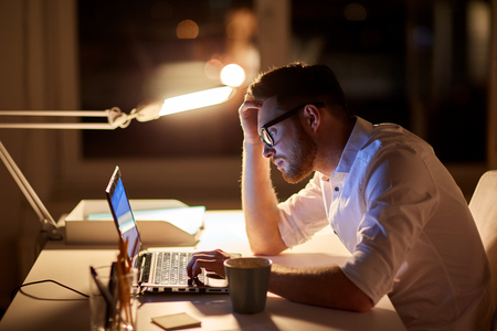 business, overwork, people, deadline and technology concept - stressed businessman in glasses with laptop computer typing at night office Stock Photo