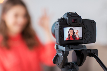 blogging, technology, videoblog, mass media and people concept - happy smiling woman or blogger with camera recording video at home and showing ok hand sign