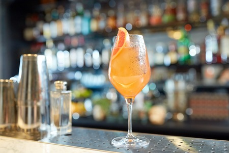 alcohol drinks and luxury concept - glass of grapefruit cocktail at bar