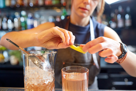 bartender with glass of cocktail and lemon at bar