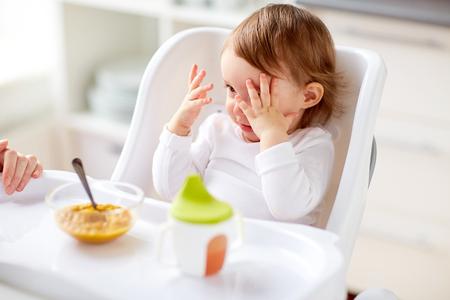 Baby zitten in kinderstoel en thuis eten