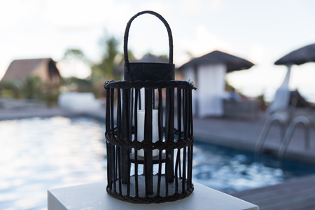 irradiation: light and summer holidays concept - lantern with extinct candle at outdoor swimming pool Stock Photo