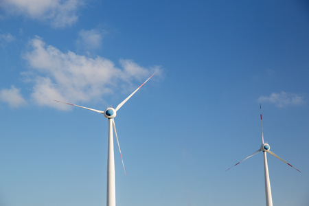renewable energy, technology and power concept - wind turbines over blue sky