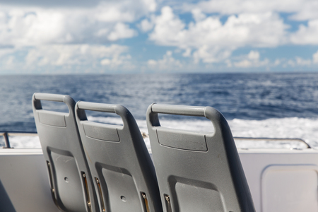 cruise travel: vacation, travel, cruise and tourism concept - seats on deck of passenger ship sailing in sea