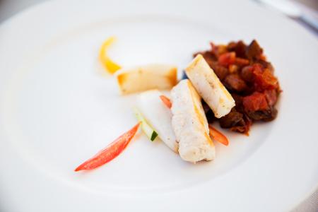 white fish with stewed eggplant garnish on plate Stock Photo