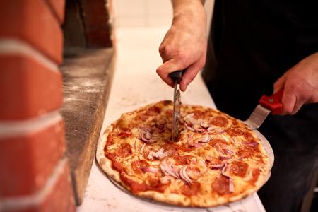 cocinar manos cortando pizza en pedazos en la pizzería