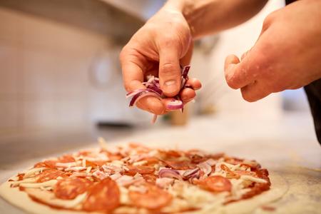 cocinar añadiendo cebolla a la pizza de salami en la pizzería