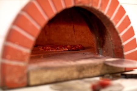 Pizza cuocere a forno alla pizzeria Archivio Fotografico - 77891763