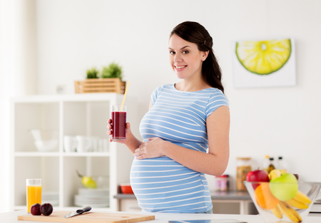 happy pregnant woman drinking juice at home