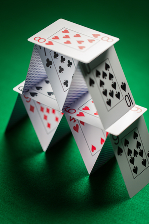 close up of house of playing cards on green cloth Imagens
