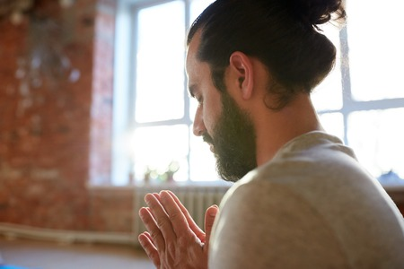 close up of man meditating at yoga studio Stock Photo