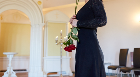 sad woman with red rose at funeral in church