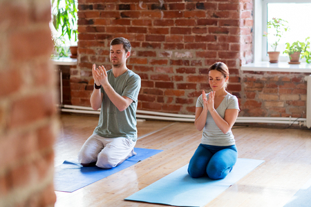 man and woman meditating at yoga studio 版權商用圖片