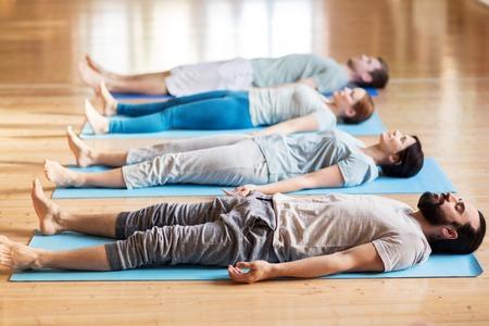 Grupo de personas haciendo ejercicios de yoga en el estudio Foto de archivo - 77931953