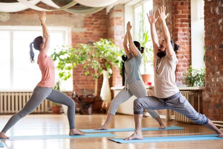 Groep mensen die yoga-krijger doen poseren in de studio Stockfoto