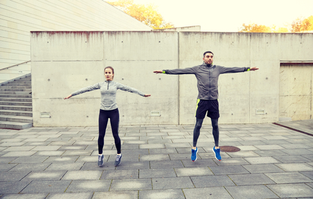 happy man and woman jumping outdoors