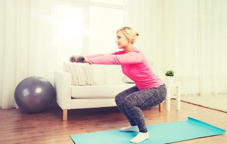 Concept de remise en forme, sport, entraînement et style de vie - femme souriante avec des haltères exercer et faire des squats à la maison Banque d'images - 78198079