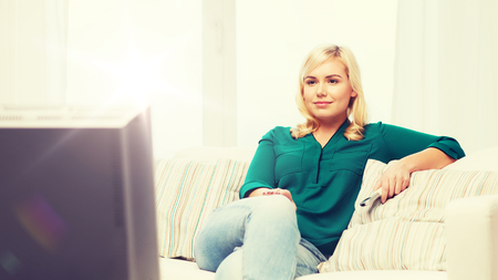 television, leisure and people concept - smiling woman sitting on couch with remote control and watching tv at home Stock Photo